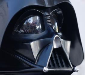"""FILE - In this file photo dated Thursday, May 12, 2005, the Los Angeles, USA, premiere of the movie """"Star Wars: Revenge of the Sith"""", is reflected in the mask eyeglasses of iconic baddie character Darth Vader. The British actor, Prowse who played Darth Vader in the original Star Wars trilogy, has died aged 85 on Saturday, according to an announcement by his agent Sunday November 29, 2020. (AP Photo/Chris Pizzello, FILE)"""