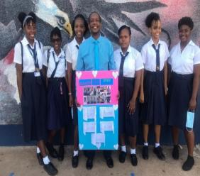 Principal of New Forest High, Arnaldo Allen, with grade 11 students who surprised him with a show of appreciation for his dedication.