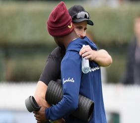 New Zealand skipper Kane Williamson (left) hugs Kemar Roach as he offers condolences on the passing of Roach's father. (Photo credit - CWI Media)