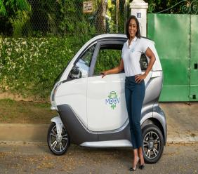 MOOV, the first electric tricycle in T&T, was launched today. In Photo, MOOV CEO Nyssa Pierre focuses with the vehicle.