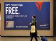 A traveler walks past a sign advertising a Delta Air Lines credit card at Seattle-Tacoma International Airport in SeaTac, Wash. Airline loyalty programs are losing much of their allure even for frequent flyers, and the rules for navigating the system have changed. (AP)