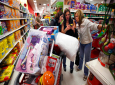 In this Nov. 28, 2014, file photo, Target shoppers Kelly Foley, left, Debbie Winslow, center, and Ann Rich use a smartphone to look at a competitor's prices while shopping shortly after midnight on Black Friday, in South Portland, Maine. (AP Photo/Robert F. Bukaty, File)