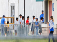In this June 20, 2018, file photo, Immigrant children walk in a line outside the Homestead Temporary Shelter for Unaccompanied Children a former Job Corps site that now houses them in Homestead, Fla. A Senate subcommittee has found that federal officials for the second time lost track of nearly 1,500 migrant children earlier this year after a government agency placed the minors in the custody of adult sponsors in communities nationwide. (AP Photo/Brynn Anderson, File)