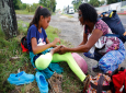 In this Sept. 2, 2018 photo, Venezuelan Sandra Cadiz inspects the foot of her 10-year-old daughter Angelis who complained of pain as they take a break from their walk to Peru along the shoulder of the road near Dagota, Colombia. (AP Photo/Ariana Cubillos)