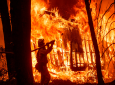 Firefighter Jose Corona sprays water as flames consume from the Camp Fire consume a home in Magalia, Calif., on Friday, Nov. 9, 2018. (AP Photo/Noah Berger, File)