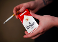 FILE - In this July 17, 2015, file photo, store manager Stephanie Hunt poses for photos with a pack of Marlboro cigarettes, an Altria brand, at a Smoker Friendly shop in Pittsburgh. (AP Photo/Gene J. Puskar, File)
