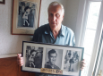 In this July 2, 2009, photo George Mendonsa poses for a photo in Middletown, R.I., holding a copy of the famous Alfred Eisenstadt photo of Mendonsa kissing a woman in a nurse's uniform in Times Square on Aug. 14, 1945, while celebrating the end of World War II, left. Mendonsa died Sunday, Feb. 17, 2019, he was 95. It was years after the photo was taken that Mendonsa and Greta Zimmer Friedman, a dental assistant in a nurse's uniform, were confirmed to be the couple. (Connie Grosch/Providence Journal via AP)