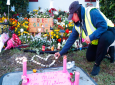 School crossing guard Wendy Behrend lights a candle at a memorial outside Marjory Stoneman Douglas High School during the one-year anniversary of the school shooting, Thursday, Feb. 14, 2019, in Parkland, Fla. A year ago on Thursday, 14 students and three staff members were killed when a gunman opened fire at the high school. (AP Photo/Wilfredo Lee)