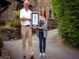In this undated handout photo provided by Guinness World Records on Tuesday, July 16, 2019, Gwyn Headley and Sarah Badhan, stand on Ffordd Pen Llech with a certificate from Guinness World Records, confirming that the road is the steepest street in the world, in the seaside town of Harlech, North Wales. A street in Wales has been designated the steepest in the world after a successful campaign by local residents. (Andrew Davies/Guinness World Records via AP)