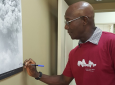 Prime Minister Dr Keith Rowley replaces his signature on a photo he shot of the La Soufrière volcano eruption in 1972.