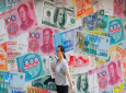 FILE - In this Aug. 6, 2019, file photo, a woman walks by a money exchange shop decorated with different countries currency banknotes at Central, a business district in Hong Kong. The IMF's latest World Economic Outlook comes on the eve of meetings in Washington this week of the IMF and its sister lending organisation, the World Bank. (AP Photo/Kin Cheung, File)