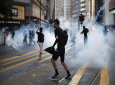 FILE - In this November 2, 2019, file photo, pro-democracy protesters react as police fire tear gas during a protest in Hong Kong. By day, the small commercial kitchen in a Hong Kong industrial building produces snacks. (AP Photo/Kin Cheung, File)