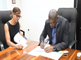 Minister of Public Infrastructure, Hon. David Patterson (Right) & Director of Paws for a Cause-Guyana, Marcia Tucker signs the MoU. Photo: Ministry of Public Infrastructure