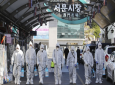 Workers wearing protective gears spray disinfectant as a precaution against the COVID-19 at a local market in Daegu, South Korea, Sunday, Feb. 23, 2020. (Im Hwa-young/Yonhap via AP)