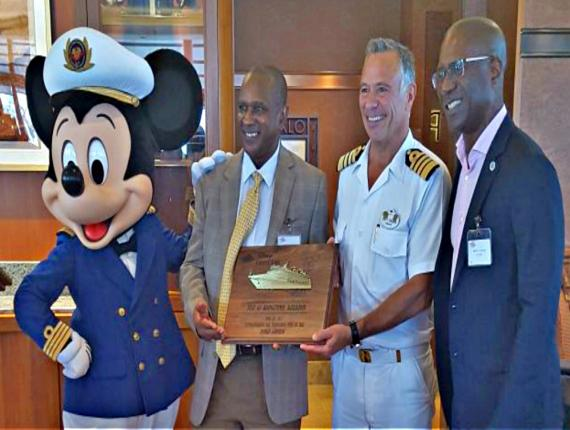 Chairman of the Barbados Tourism Marketing Inc., Alvin Jemmott (second left), presenting the traditional Barbados mahogany plaque to Captain Fabian Dib, joined by CEO of Barbados Port Inc., David Jean-Marie, and Disney mascot, Mickey Mouse.