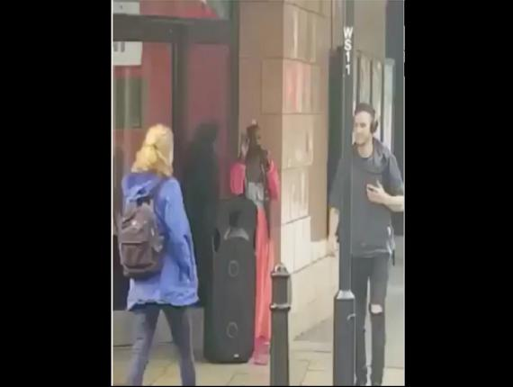 Screenshot of a video showing a woman singing on a sidewalk while commuters walk by in Europe.
