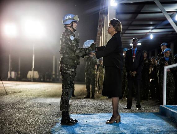 La cheffe de la MINUSTAH, Sandra Honoré, reçoit le drapeau onusien des mains d'un soldat lors du départ du bataillon brésilien en septembre dernier. Crédit photo : Facebook/MINUSTAH.