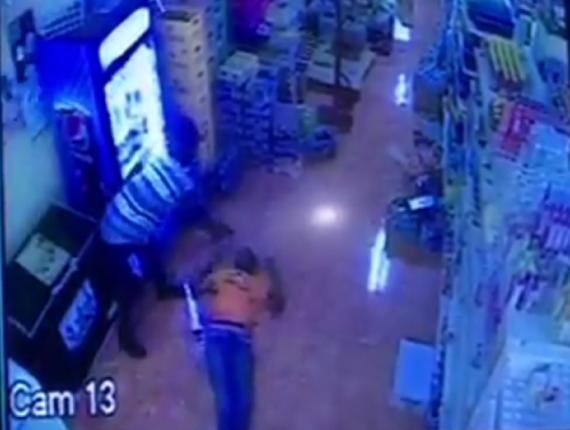 Screenshot of the video showing a man pumping bullets into the body of Ochille Hall inside a supermarket in Westmoreland.