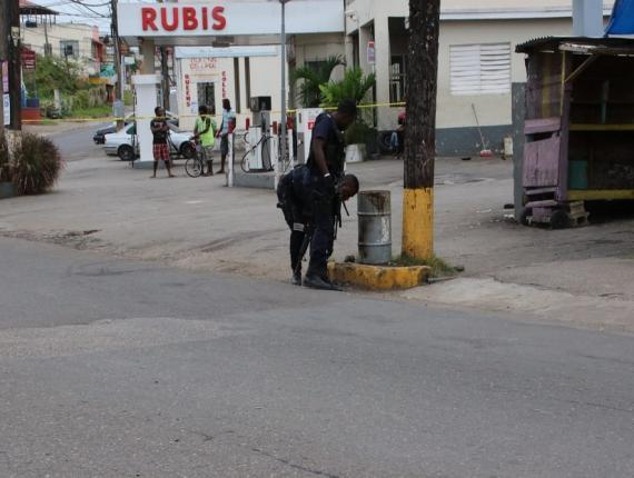 Police personnel examine the scene outside a supermarket at Guinep Tree in May Pen, Clarendon where heavily armed robbers were thwarted by police personnel on Sunday morning, but not before two lawmen were shot and injured in the gunfight.