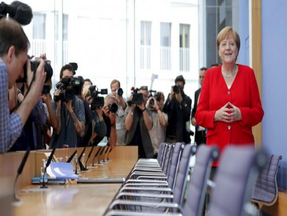 German Chancellor Angela Merkel, right, smiles as she arrives for her annual sommer press conference in Berlin, Germany, Friday. (AP Photo)