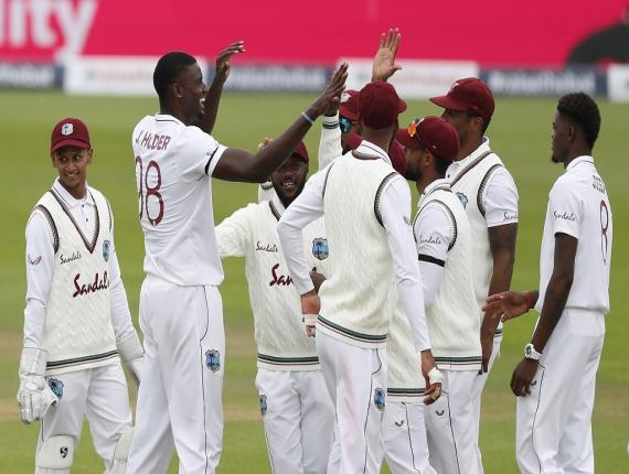 West Indies' captain Jason Holder, second left, celebrates with teammates the dismissal of England's Jofra Archer during the second day of the first cricket Test match at the Ageas Bowl in Southampton, England, Thursday, July 9, 2020.(Adrian Dennis/Pool via AP).