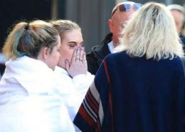 Fan leaves the Park Inn hotel in central Manchester, England, Tuesday, May 23, 2017. Twenty two people were killed in an explosion following a Ariana Grande concert at the Manchester Arena late Monday evening