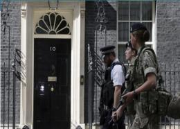 Members of the army join a police officer outside 10 Downing Street in London, Wednesday, May 24, 2017. Britons will find armed troops at vital locations Wednesday after the official threat level was raised to its highest point following a suicide bombing that killed more than 20, as new details emerged about the bomber.