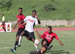 Rivoli's Fabian Gordon (right) challenges Swayne Thomas (centre) of Cavalier during their  Magnum/Charley's JB JFF Premier League play-off match at Stadium East on Wednesday. Rivoli's goalscorer Mario Mathenson gets ready to join the action. The game ended 1-1.
