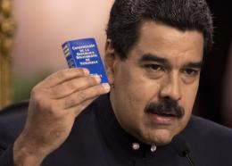 Venezuela's President Nicolas Maduro holds a copy of the constitution, as he speaks during a news conference in Caracas, Venezuela, Tuesday, Aug. 22, 2017. Immigration authorities in Colombia announced that Venezuela's ousted chief prosecutor Luisa Ortega Diaz is on her way to Brazil. Ortega said that Maduro removed her in order to stop a probe linking him and his inner circle to nearly $100 million in bribes from Brazilian construction company Odebrecht.