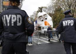 """Police officers stand near the site where a large balloon of Olaf, from the animated film, """"Frozen"""", is being inflated for the Thanksgiving Day parade in New York, Wednesday, Nov. 22, 2017."""
