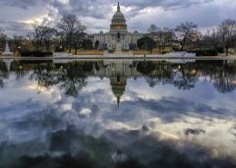 Clouds are reflected in the U.S. Capitol reflecting pool at daybreak in Washington as Day Three of the government shutdown continues, Monday, Jan. 22, 2018. (AP Photo/J. David Ake)
