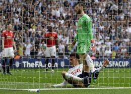 Tottenham's Dele Alli lands inside the goal after scoring the opening goal during the English FA Cup semifinal football match against Manchester United  at Wembley stadium in London, Saturday, April 21, 2018.