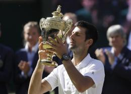 Serbia's Novak Djokovic lifts the trophy after winning the men's singles final match against Kevin Anderson of South Africa, at the Wimbledon Tennis Championships, in London, Sunday July 15, 2018.(AP Photo/Kirsty Wigglesworth).