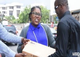 Blind street singer, Michael Brown (right), receives one of two laptop computers which were presented to him for his two daughters by Deleen Powell, Marketing and Public Relations Manager at Universal Service Fund (USF) in response to a Loop News story on Brown's challenges and aspirations, which was carried on Sunday.