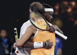 Spain's Rafael Nadal, front, is congratulated by United States' Frances Tiafoe after defeating him in their quarterfinal match at the Australian Open tennis championships in Melbourne, Australia, Tuesday, Jan. 22, 2019.