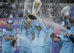 England's captain Eoin Morgan is sprayed with champagne as he raises the trophy after winning the Cricket World Cup final match between England and New Zealand at Lord's cricket ground in London, Sunday, July 14, 2019. England won after a super over after the scores ended tied after 50 overs each. (AP Photo/Matt Dunham)