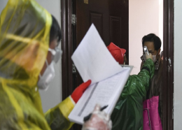 In this Feb. 18, 2020, photo released by Xinhua News Agency, workers go door to door to check the temperature of residents during a health screening campaign in the Qingheju Community, Qingshan District of Wuhan in central China's Hubei Province.  (Cheng Min/Xinhua via AP)