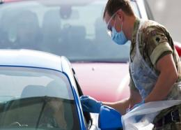 An NHS (National Health Service) worker is tested for COVID-19 by a soldier at a drive-through testing centre, in Manchester, northern England, Thursday, April 9, 2020. (AP Photo/Jon Super)