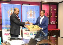 Tourism Minister, Edmund Bartlett (left), presents laptops and cell phones to Minister of State in the Ministry of Industry, Commerce, Agriculture and Fisheries, Floyd Green, during a digital press briefing on April 2 to provide an update on the tourism sector.