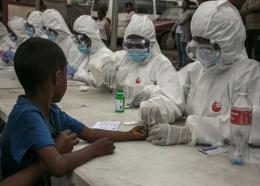 Des agents de santé prélèvent des échantillons de sang d'un enfant pour détecter le coronavirus, à Antananarivo le 3 avril 2020. AFP / RIJASOLO