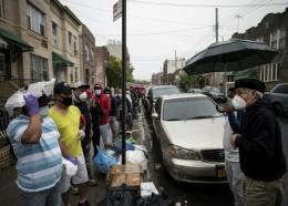 Le pasteur new-yorkais Fabian Arias (à droite) parle à des Guatémaltèques venus profiter d'une distribution de nourriture qu'il organise pour les immigrés hispaniques, le 22 mai 2020 à Harlem