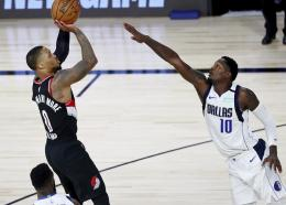 Portland Trail Blazers guard Damian Lillard (0) shoots as Dallas Mavericks forward Dorian Finney-Smith (10) attempts to block during the second half of an NBA basketball game Tuesday, Aug. 11, 2020, in Lake Buena Vista, Fla. (Kim Klement/Pool Photo via AP).