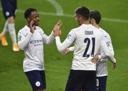 Manchester City's Ferran Torres, right, celebrates with Raheem Sterling (left) after scoring his side's third goal during the EFL Cup 4th round football match against Burnley at Turf Moor in Burnley, England, Wednesday, Sept. 30, 2020. (Paul Ellis/Pool via AP).