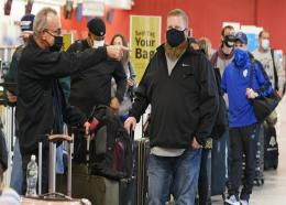 Travelers wait in line at the ticket counter before traveling from Cleveland Hopkins International Airport, Wednesday, November 25, 2020, in Cleveland. (AP Photo/Tony Dejak)