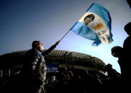 Un homme avec un drapeau orné d'une photo de Diego Maradona devant le stade de Naples le 26 novembre 2020 Filippo MONTEFORTE AFP/Archives