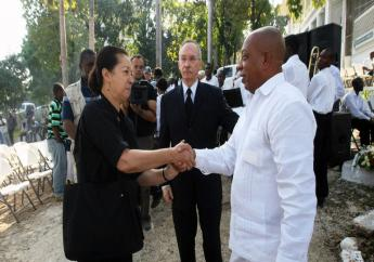 Michèle Montas donnant une poignée de main à un officiel haïtien