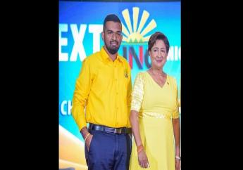 Chairman of the National Youth Arm of the United National Congress Kaveesh Siewdial standing alongside political leader of the United National Congress Kamla Persad-Bissessar.