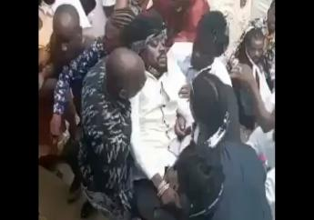 Screengrab of a video showing entertainer Beenie Man being ferried away by men after he fainted at his mother's funeral on Sunday.
