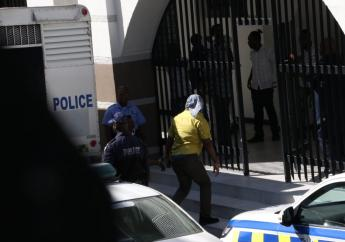 A convicted member of the Uchence Wilson gang being escorted onto the Supreme Court building yesterday.