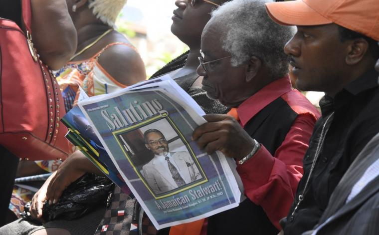 A man reads a newspaper supplement with a photo of the late Easton Douglas on the cover at Douglas' funeral at the St Andrew Parish Church on Thursday. (PHOTOS: Marlon Reid)